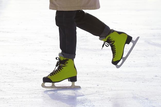 아이스 링크에서 스케이트에 여성 다리입니다. 스포츠 및 엔터테인먼트. 휴식과 겨울 방학.
