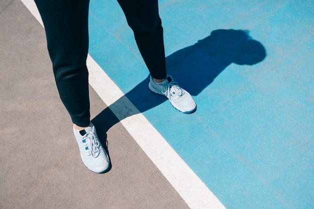 Женские ножки в кроссовках и черных спортивных штанах