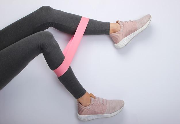 白い表面にフィットネスエラスティックでエクササイズをしているスポーツレギンスやスニーカーの女性の脚。上面図