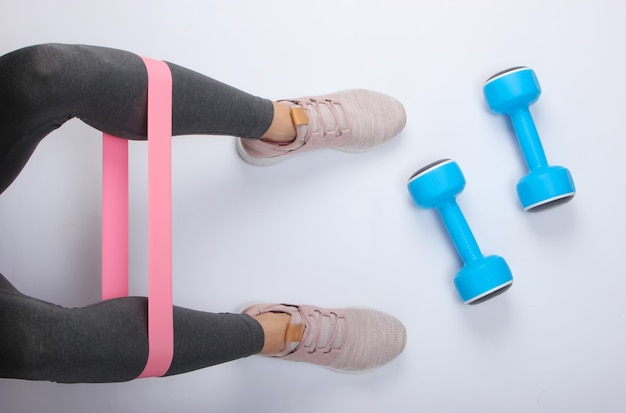 ダンベルで白い表面にフィットネスエラスティックでエクササイズをしているスポーツレギンスやスニーカーの女性の脚。上面図