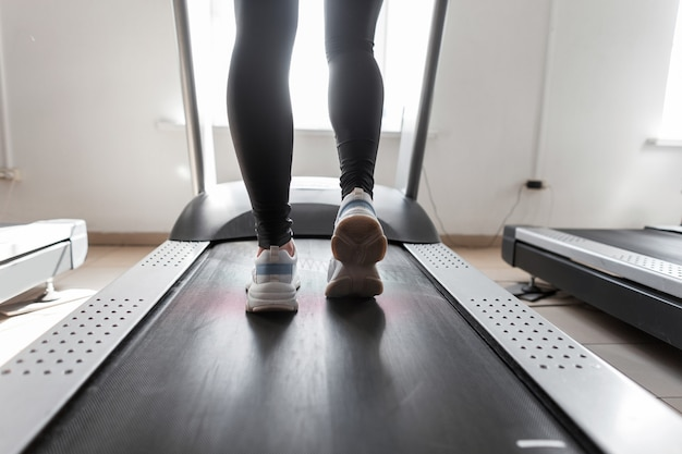 ジムのスポーツシューズの女性の脚。トレッドミルで走っている女性