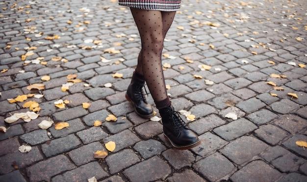 Женские ножки в трико и сапогах гуляют по городской брусчатке с опавшими осенними листьями.