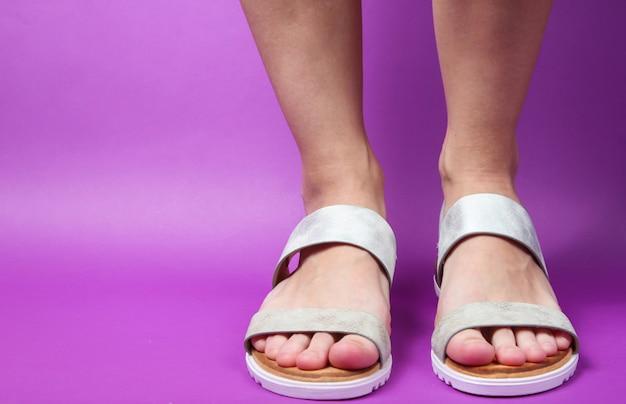 紫のトレンディなレザーサンダルで女性の足。夏の靴。