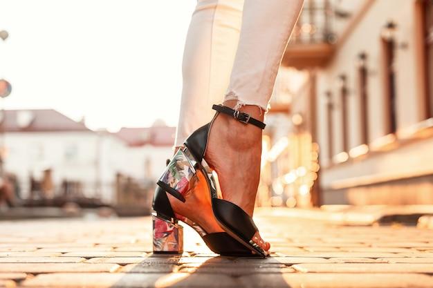 우아한 가죽 샌들에 흰색 청바지에 여성 다리 일몰에 도시에 서 있습니다. 확대