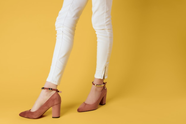 クローズアップ孤立した背景ポーズの白いズボンの靴の女性の脚