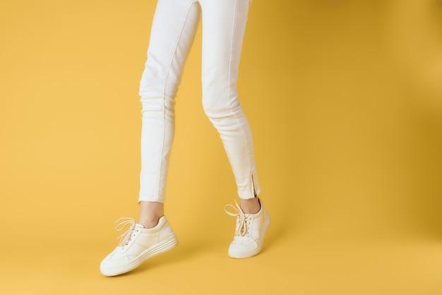 白いズボンのスニーカーの女性の脚は黄色の背景をファッションします