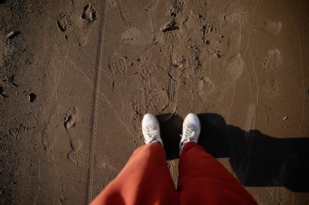 젖은 모래에 흰색 운동화와 주황색 바지에 여성 다리