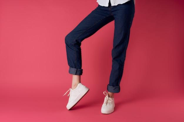白いスニーカーの逆さまのビューピンクの背景ファッションの女性の脚