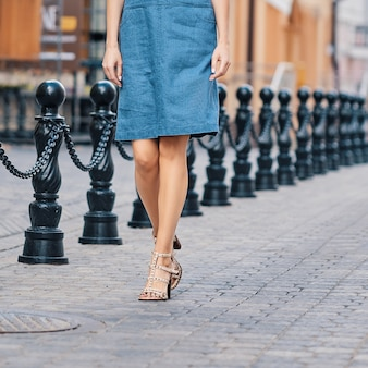 Female legs in jeans skirt
