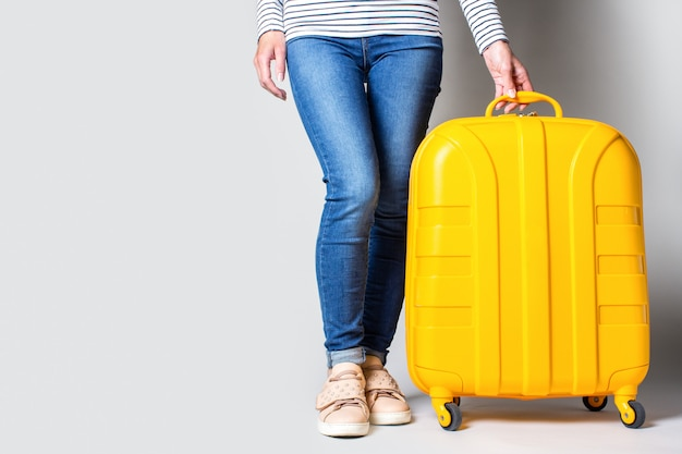 Female legs in jeans stand next to a yellow suitcase on a light background