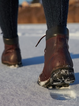 Female legs in leather brown waterproof boots is hiking in for winter on fresh snow. casual fashion, trendy footwear.