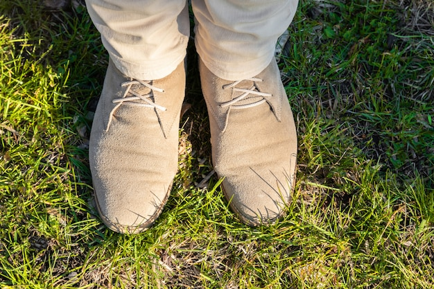 Female legs in light trousers with beige shoes on green grass on a sunny day