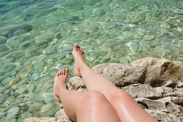 Female legs near clean sea with stone. clean water. summer vacation. close up.
