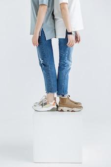 スニーカーとジーンズのスタジオでカジュアルな服のクローズアップの新しいコレクションに立っている2つのモデルの女性の女性の脚