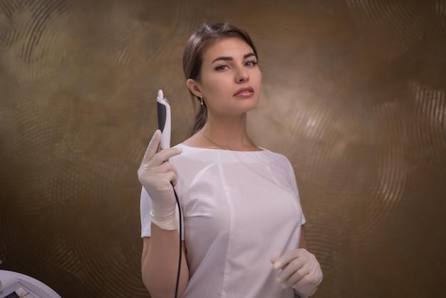手袋をはめたプロの美容師による脱毛中の紫色のシーツの女性の脚。スパ、美容業界、クリニックでのトリートメント、電気分解。