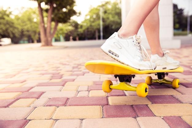 スケートボードの女性の足