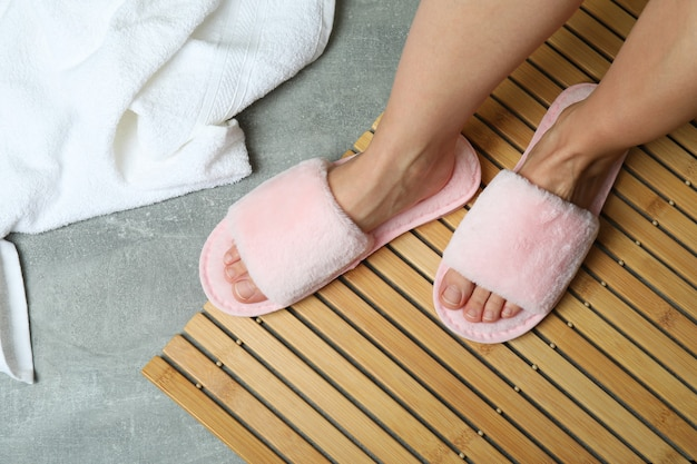 Female legs in pink slippers on bamboo on gray floor