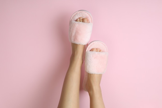Female legs in pink slippers on pink