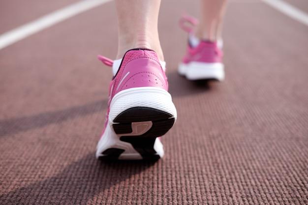 Female legs in pink sneakers on running track stadium