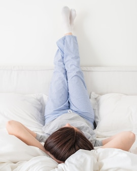 Female legs raised up high and arms under her head lying on bed in bedroom wearing pajamas