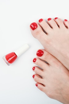 Female legs and red nail polish on a white space.