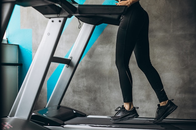 Female legs on the running track at the gym