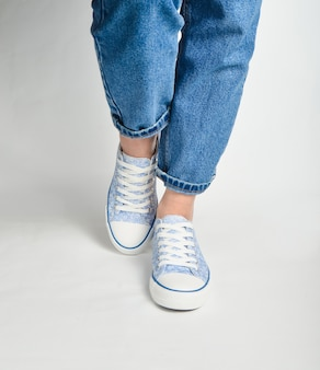 Female legs in short jeans and sneakers stand on a white