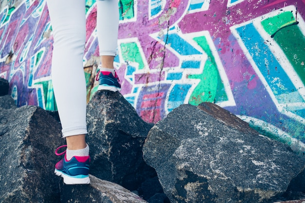 Female legs in sneakers and jeans climb over the rocks on the surface of a graffiti wall