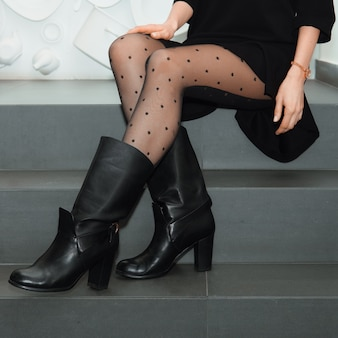 Female legs in tights and boots on stairs