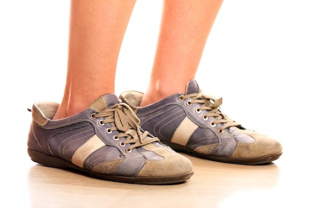 흰색 배경 위에 너무 큰 남성 신발에 노력하는 여성 다리