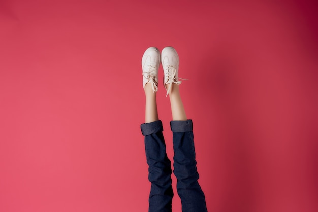 Female legs upside down cropped view pink background fashion