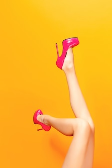 Female legs wearing summer high heels over yellow backgroundd