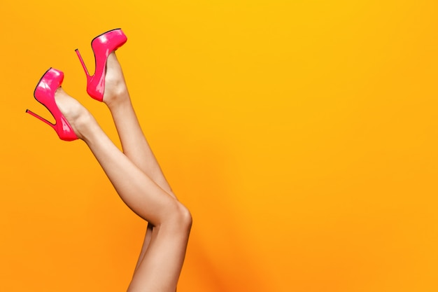Female legs wearing summer high heels over yellow scene