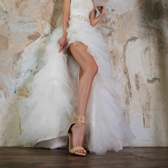 Female legs in wedding dress leaning to the wall