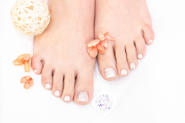 Female legs on a white background. nails get a fresh and neat look during the pedicure procedure.