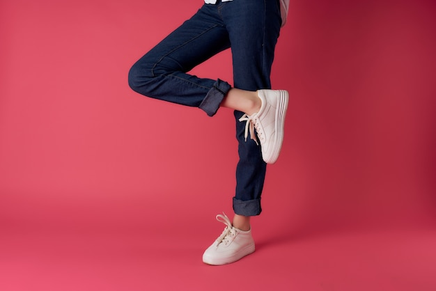 Female legs in white sneakers in fashion posing pink background