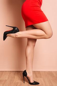 Женские ножки с черными туфлями на высоких каблуках на розовом фоне стены - изображение