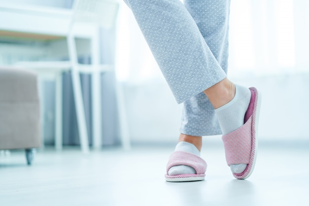 Female legs with cozy soft comfortable home slippers