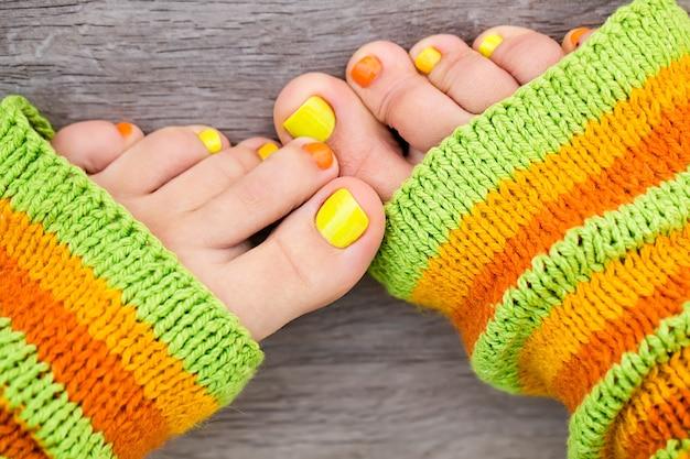 Женские ножки с педикюром и красочным текстилем