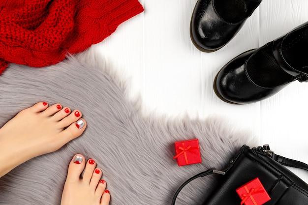 Женские ножки с красными ногтями и туфлями на сером пушистом одеяле.