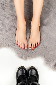 Женские ножки с красными ногтями и туфлями на сером пушистом одеяле