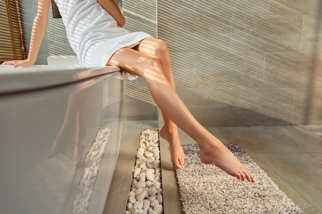 Female legs with yellow nail design in bathroom with sunlight