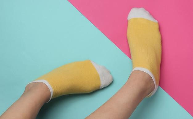 ピンクブルーのスタジオの背景に黄色の靴下と女性の脚パステルカラートレンドミニマルなファッションコンセプト