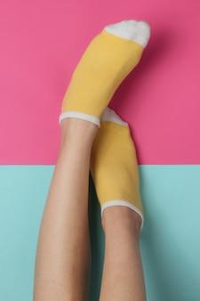 ピンクブルーのスタジオの背景に黄色の靴下と女性の脚