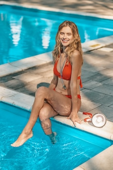 A female lifeguard in na red swimmimng suit near the pool