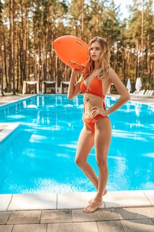 Female lifeguard in a red swimming suit standing near the public swimming pool