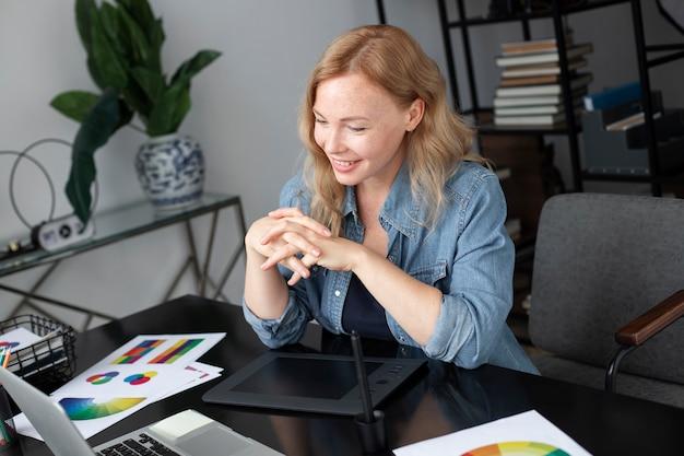 사무실에서 그래픽 태블릿으로 일하는 여성 로고 디자이너