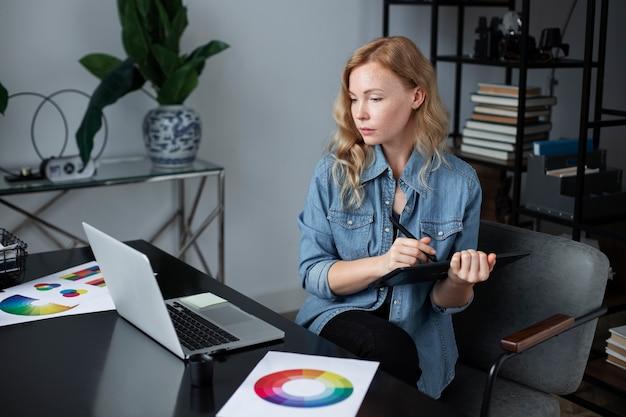 Женский дизайнер логотипов работает в своем офисе на графическом планшете