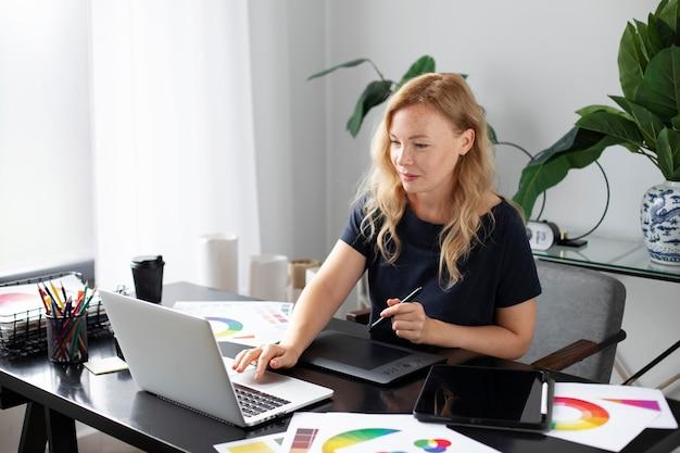 Женский дизайнер логотипов работает над своим планшетом, подключенным к ноутбуку