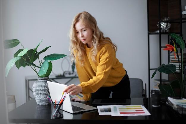 노트북에 연결된 태블릿에서 작업하는 여성 로고 디자이너
